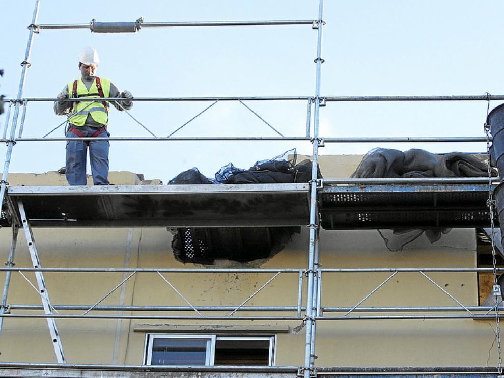 Los operarios están trabajando en la colocación del andamio sobre la fachada que quedó en pie