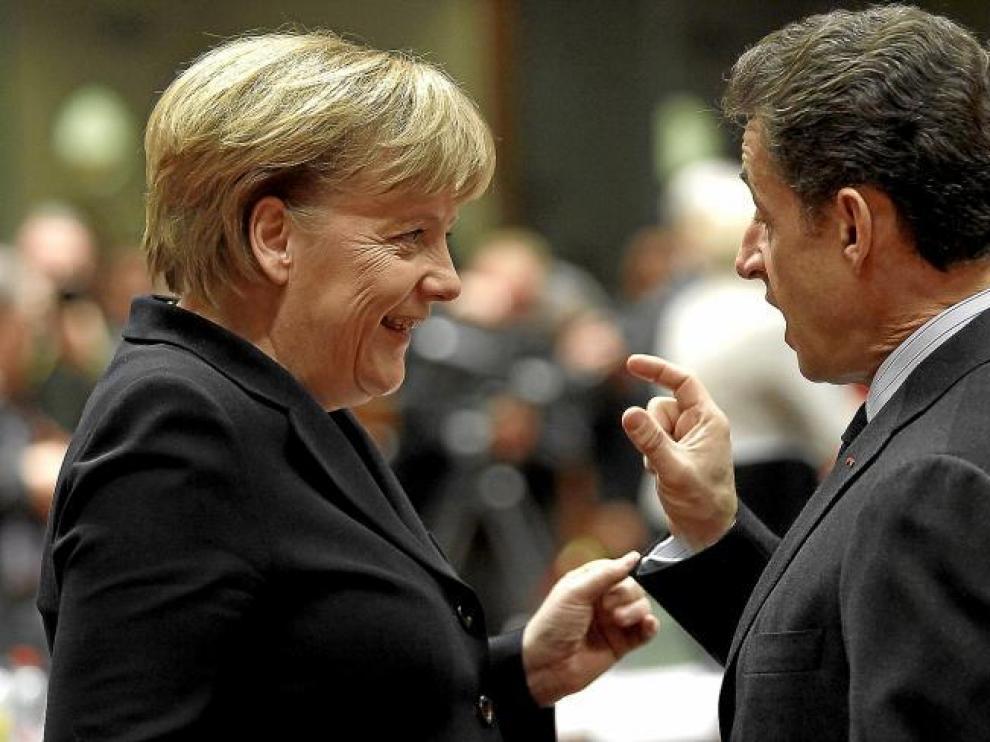 La canciller alemana, Angela Merkel, conversa con el presidente francés, Nicolas Sarkozy, ayer en Bruselas.