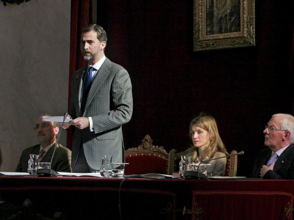 El Príncipe pronuncia su discurso junto a la prencesa Letizia y el director saliente de la RAE, Víctor García de la Concha.