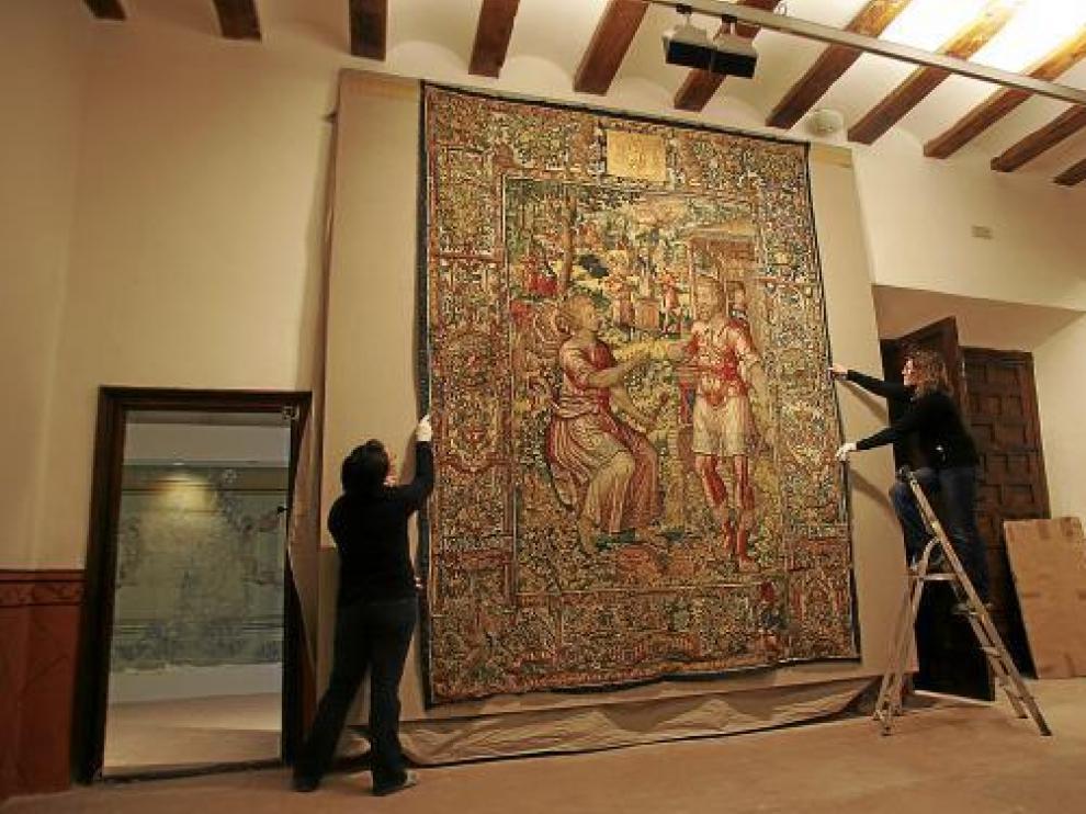 Dos trabajadoras de la Fundación colocan un tapiz en el Museo Episcopal.