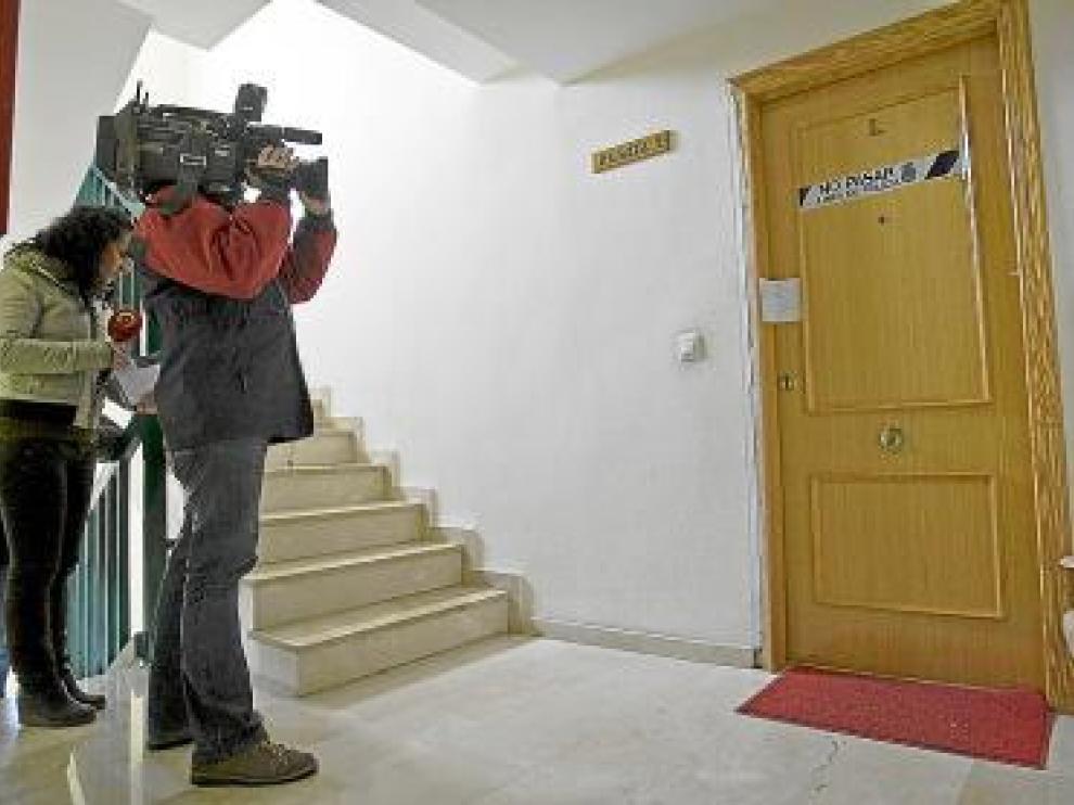 Dos periodistas, en la puerta de entrada de la vivienda.