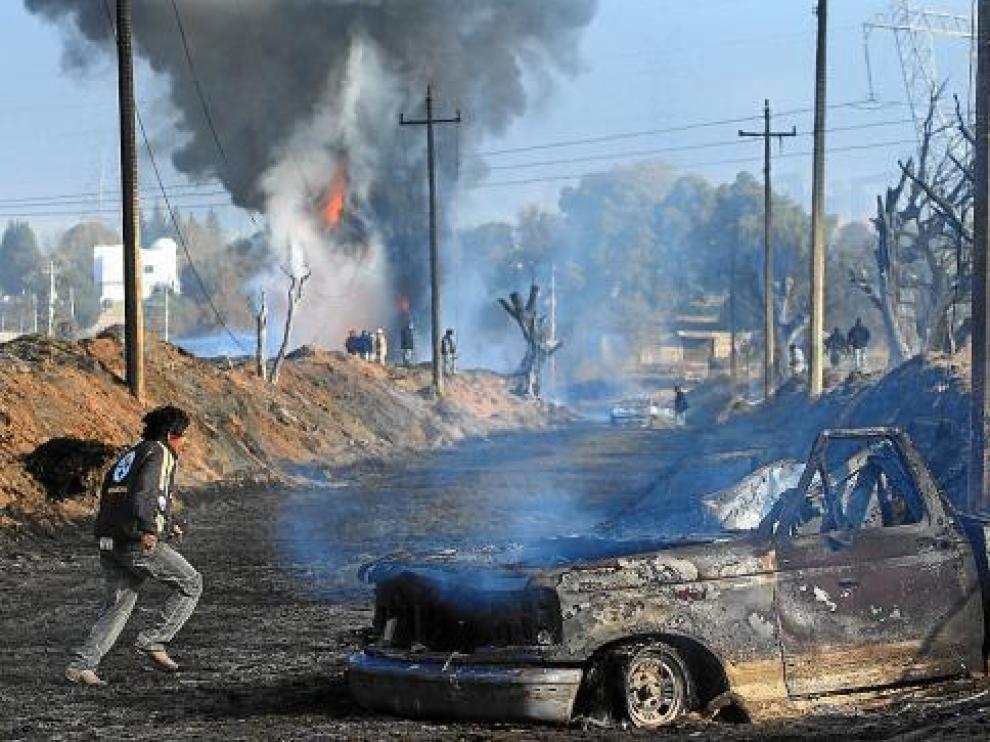 Algunos vecinos observan camiones incendiados tras la explosión en San Martín Texmelucan.