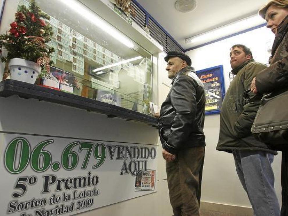 Varios clientes hacen cola ayer en una administración de lotería de Huesca.