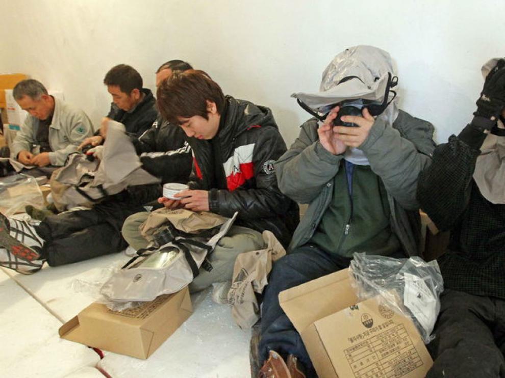 Varias personas se ponen máscaras antigas en el interior de un refugio en la Isla Yeonpyeong