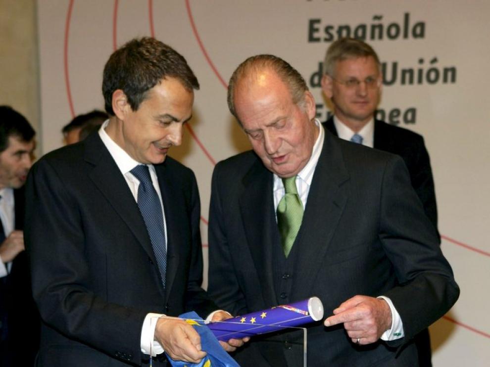 El presidente del Gobierno, Jose Luís Rodríguez Zapatero muestra al rey el distintivo que acredita a España en la presidencia de la UE