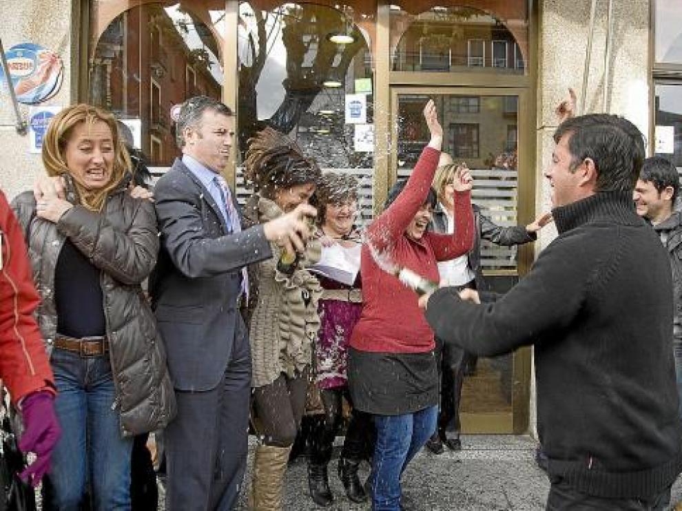 El propietario del bar Rioja, situado junto a la peluquería, riega de champán a varias personas.