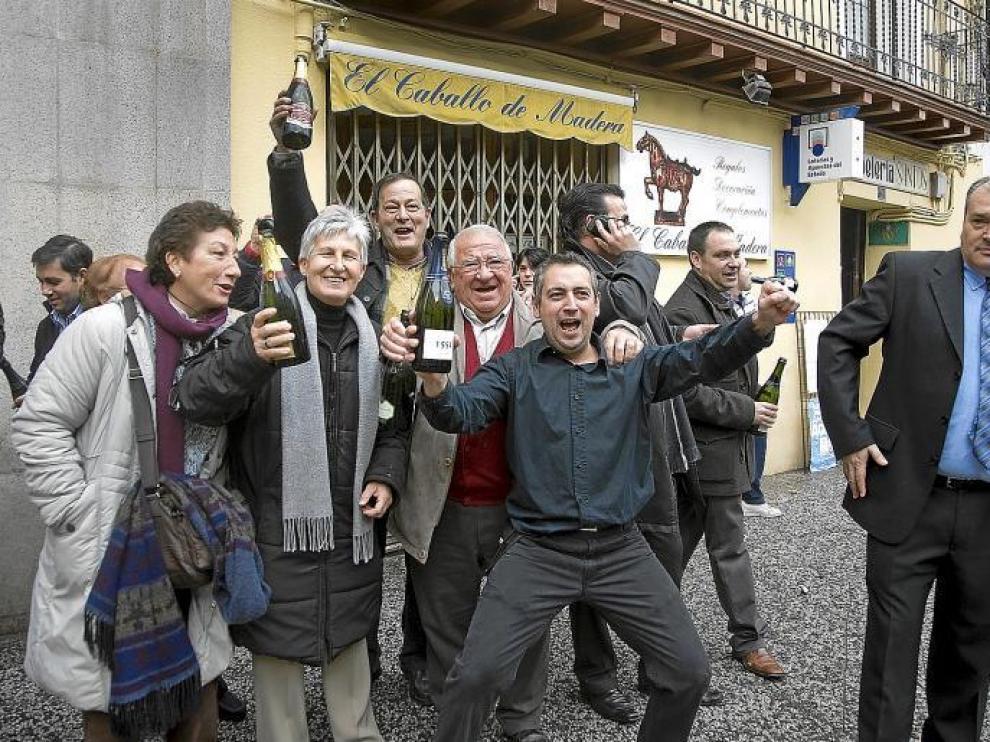 El peluquero José Luis Vicén (en el centro) celebra el premio con una botella en la mano y acompañado de varios afortunados.