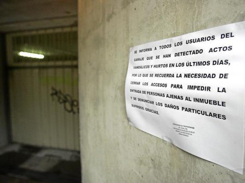 Un cartel alerta a los vecinos de un bloque del Polígono 24 de Huesca de los hurtos en garajes.