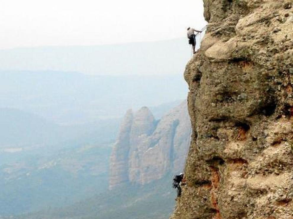 Una cordada en Peña Rueba, con los Mallos de Agüero al fondo de la imagen. A la derecha, el cartel con la prohibición de escalar.