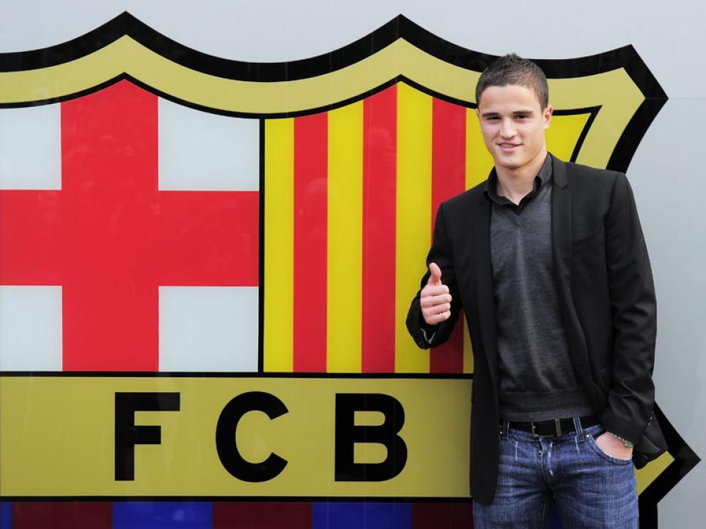Afellay posa con el escudo del Barça tras él