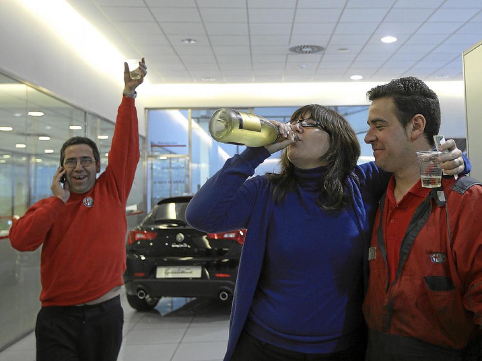 Trabajadores de Alfa Romeo celebran que les ha tocado el 2º premio de la lotería. Algunos empleados tienen más de tres décimos.