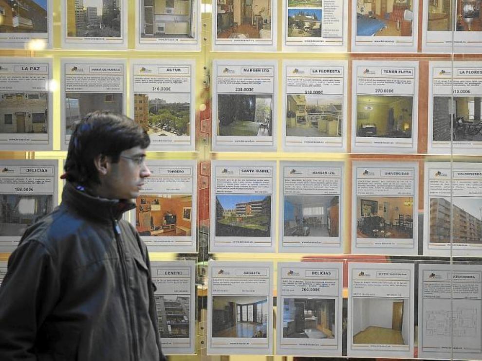 Un ciudadano pasando por delante de una inmobiliaria