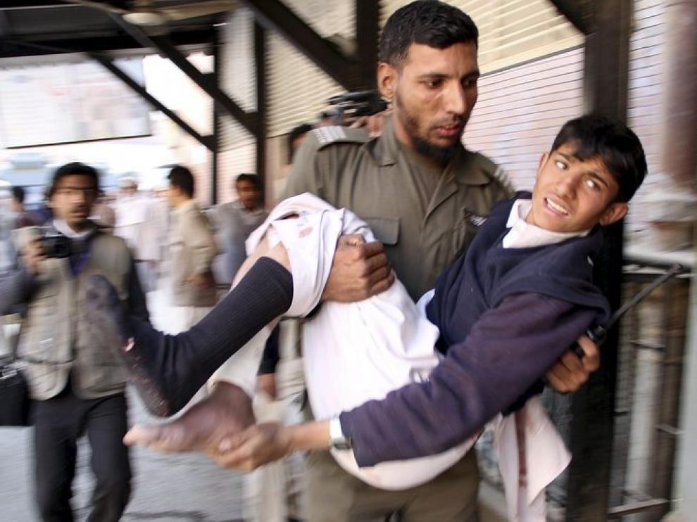 Un soldado traslada a un joven herido en el atentado de Khar