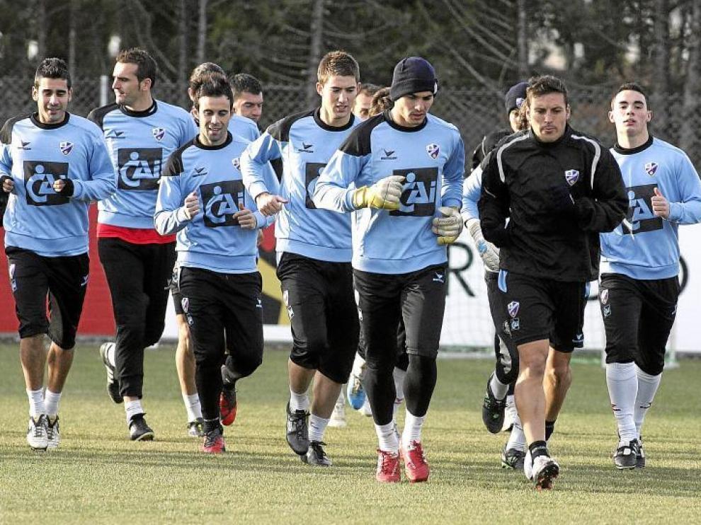 Algunos de los futbolistas de la Sociedad Deportiva Huesca, durante el entrenamiento de ayer en el IES Pirámide.