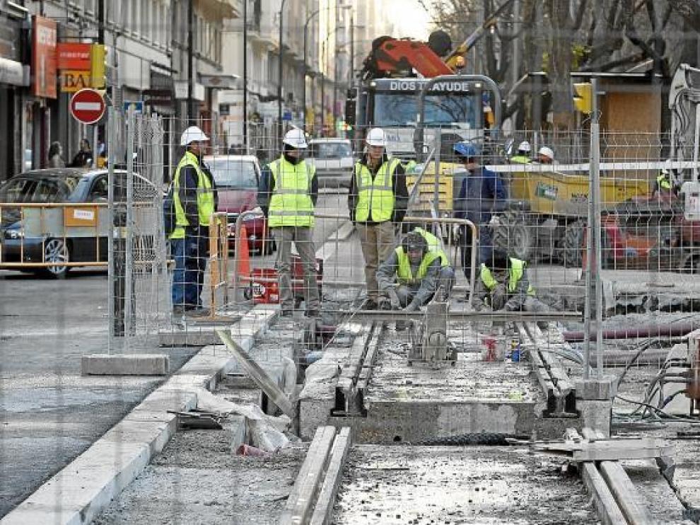 Varios operarios contemplan los trabajos, con un tramo de carril retirado en primer término.