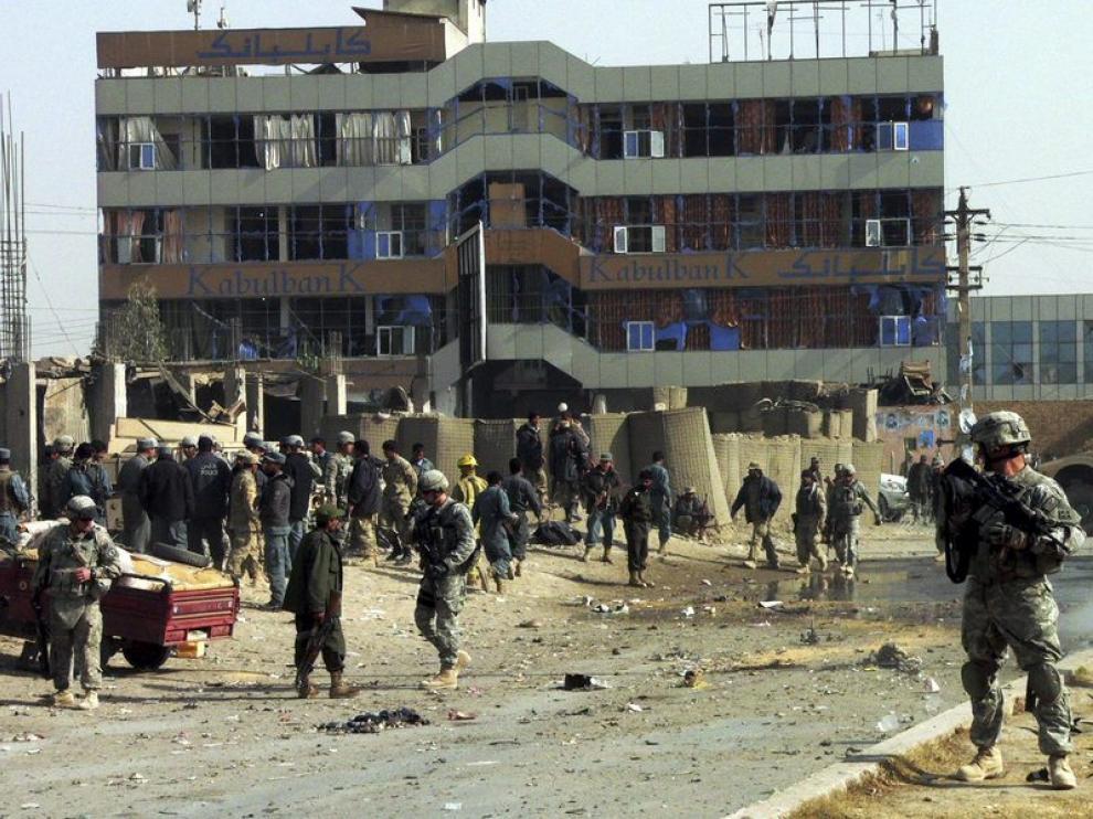 Los soldados estadounidenses y afganos inspeccionan el lugar en el que ha sucedido el atentado suicida, hoy en Kandahar
