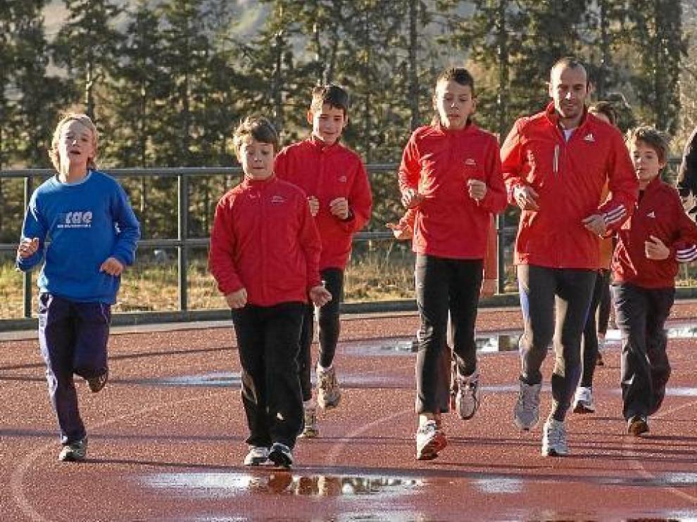 Roberto García y Toni Abadía, con un grupo de atletas en las pistas de la Ciudad Deportiva de Ejea el año pasado.
