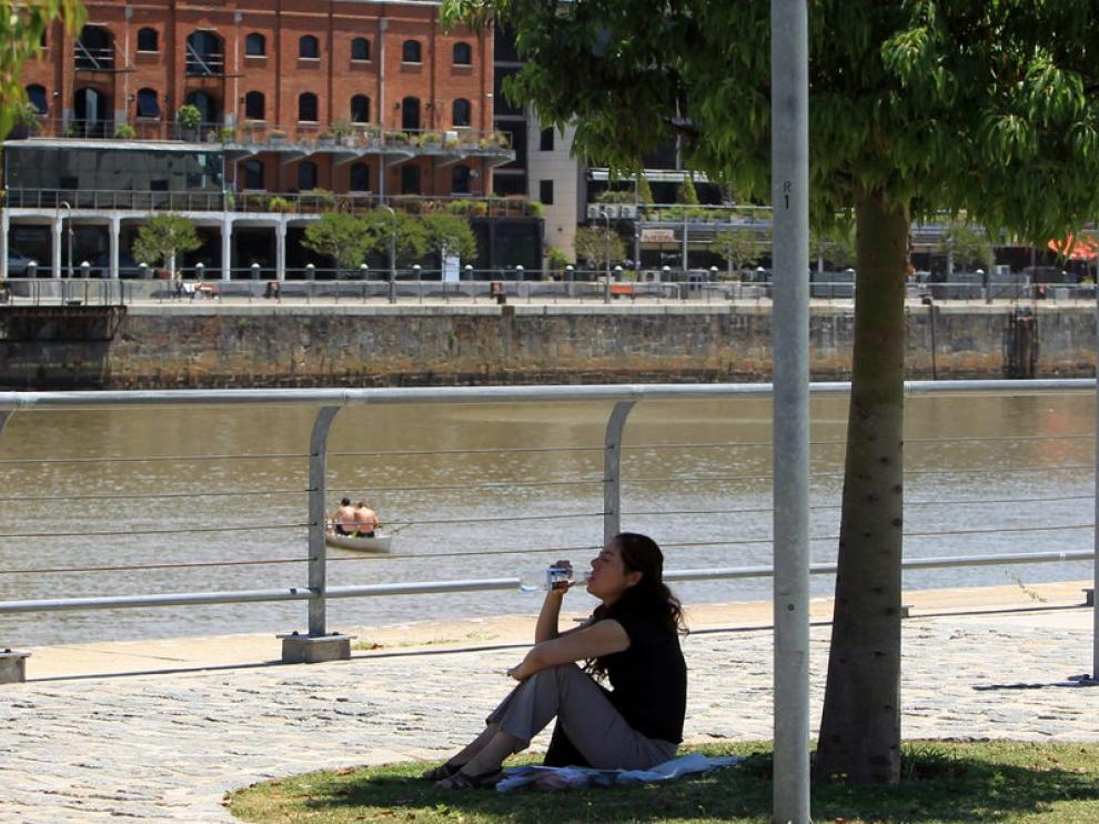Una mujer se refresca a la sombra de un árbol, hoy en Buenos Aires