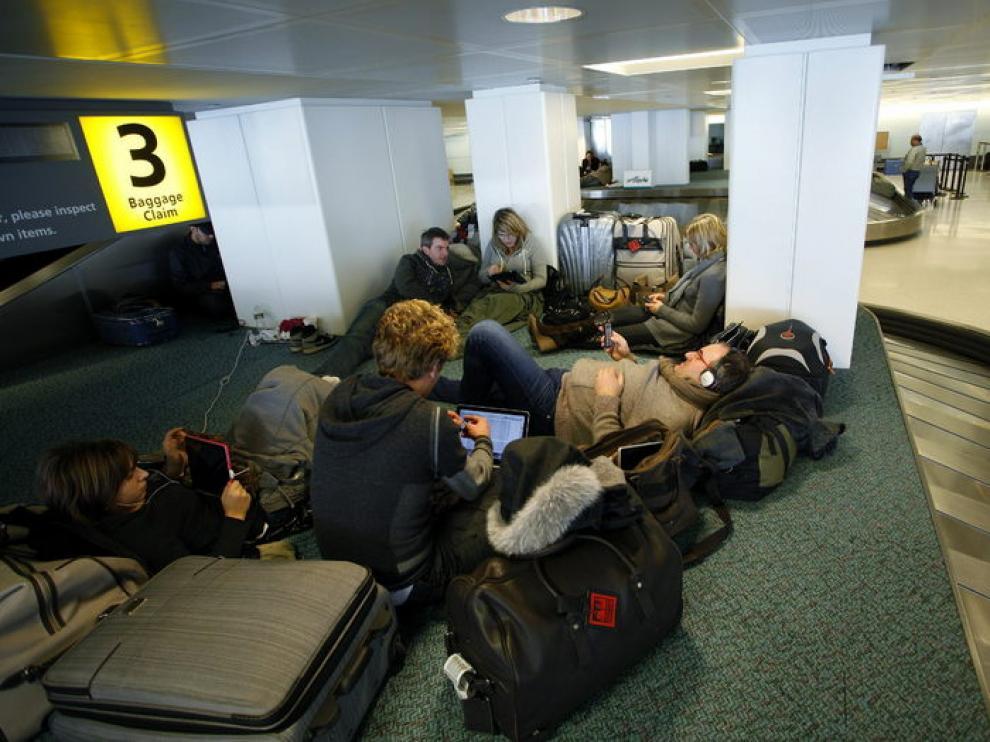Varios pasajeros acampan mientras esperan para embarcar en el aeropuerto de París.