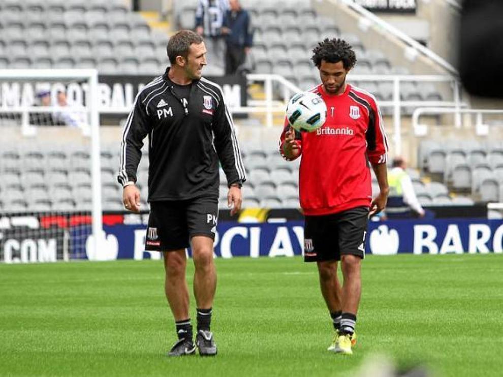 Pennant, tras un calentamiento, junto a uno de los técnicos del Stoke City.