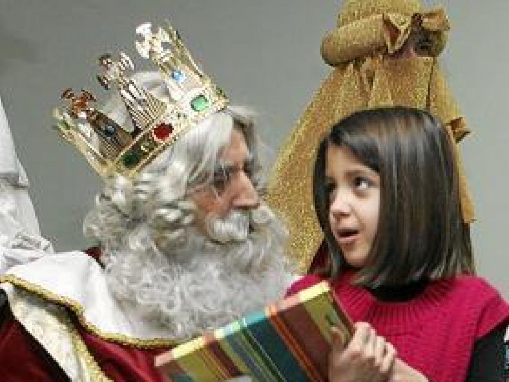 Melchor entrega un regalo a una niña, en una imagen de archivo