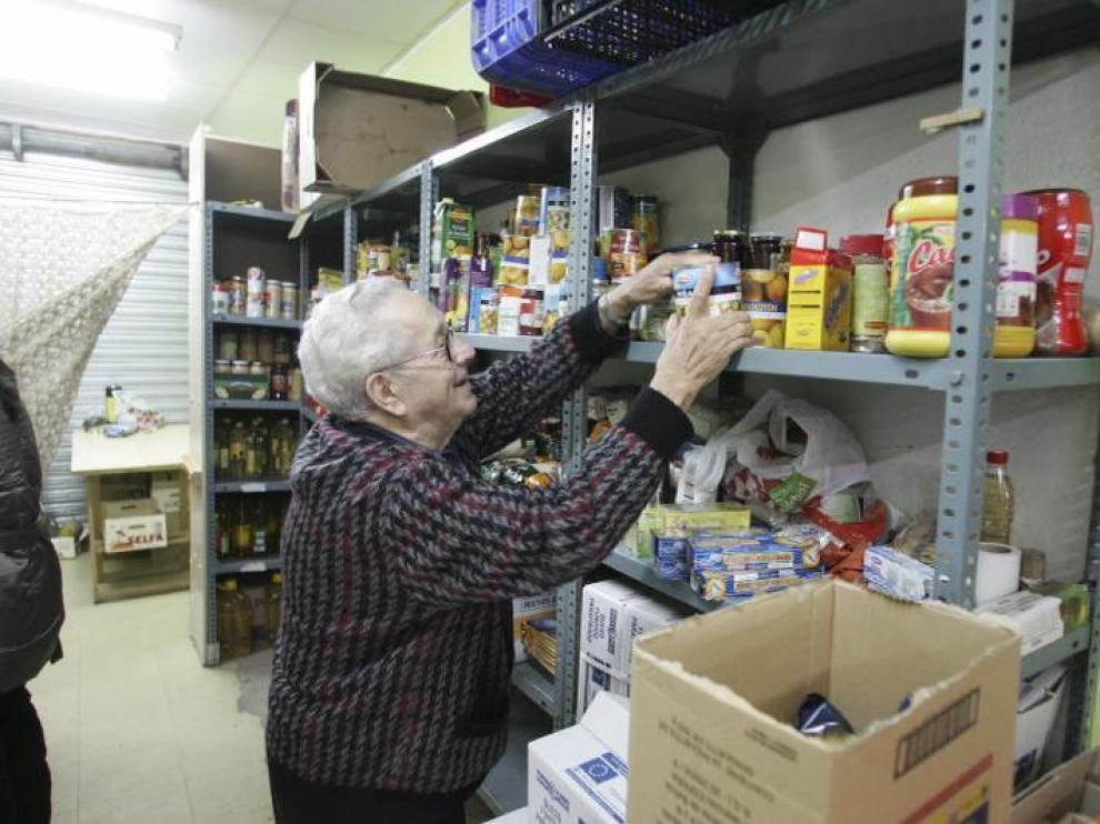 Un voluntario, en la sede de San Lorenzo, coloca los diferentes alimentos que han recibido.