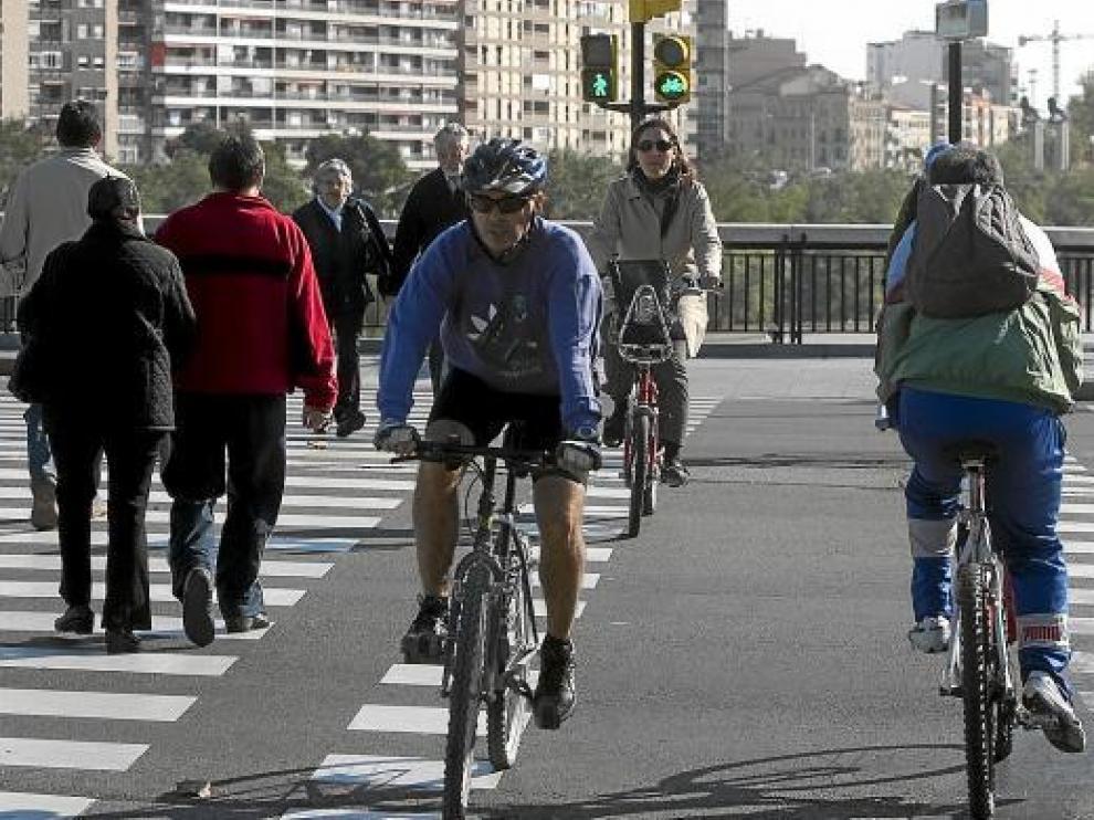 Tres ciclistas en un paso regulado por semáforos junto al puente de Santiago.