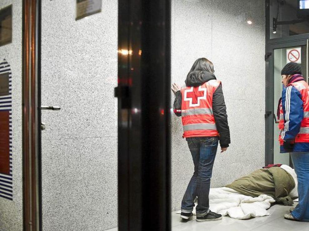 Dos voluntarios de Cruz Roja atienden a una persona sin hogar en Zaragoza.