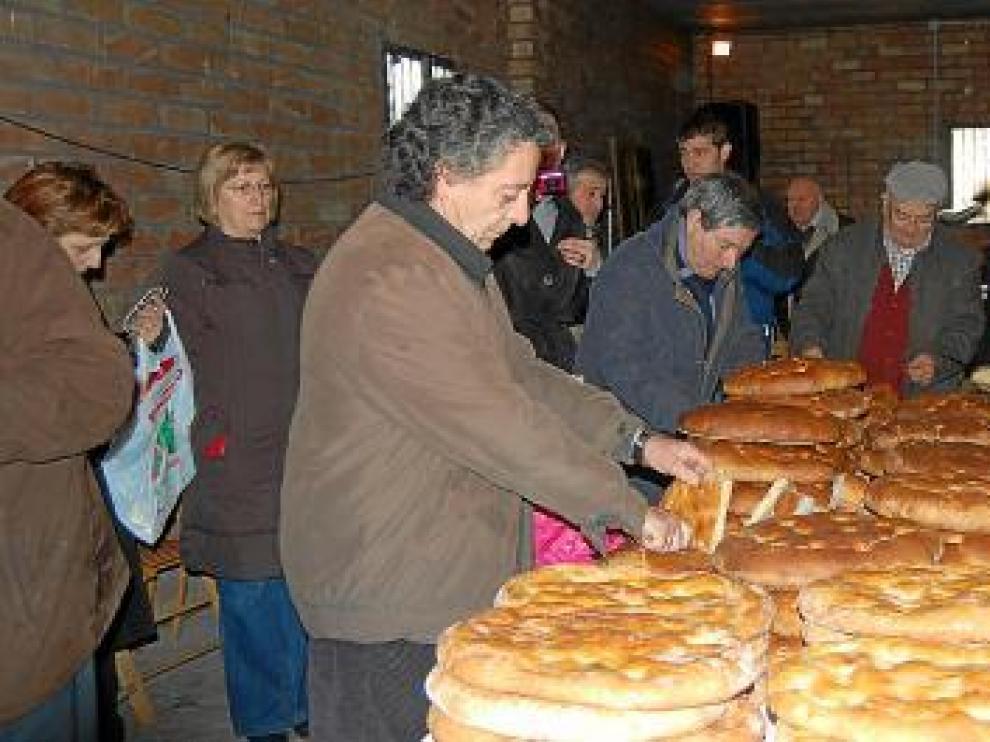 Tras la bendición, varios vecinos cortan las tortas y las reparten entre el público.