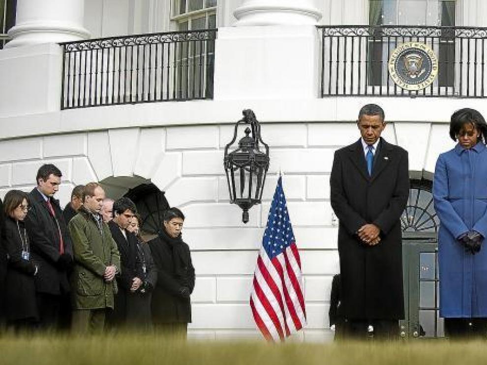 El presidente de Estados Unidos, Barack Obama (centro), y su esposa, Michelle, guardan un minuto de silencio, ayer en la Casa Blanca en Washington.