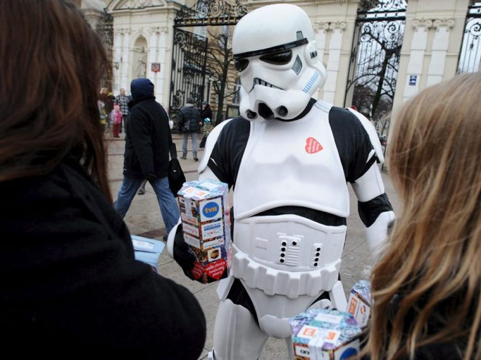 Dos jóvenes se acercan a un voluntario disfrazado de personaje de 'Star Wars' para realizar su donación