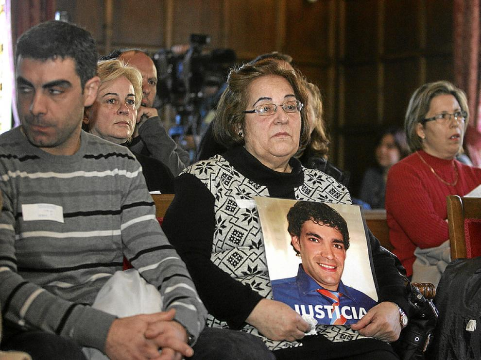Julia Bernad, sentada entre el público, abraza la foto de su hijo en la que pide Justicia.