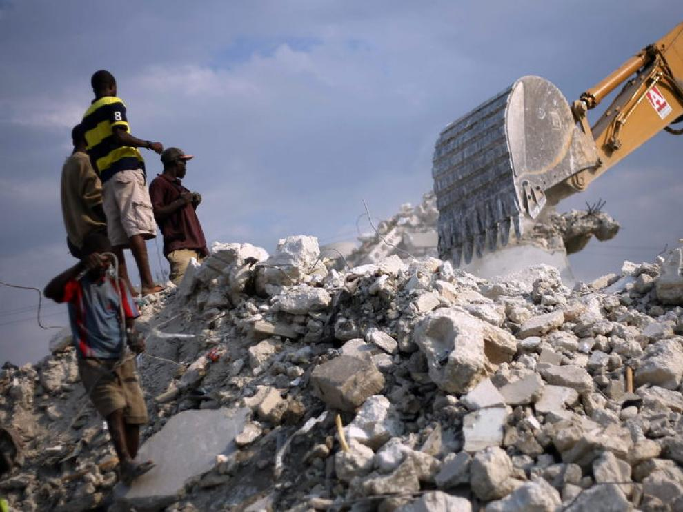 Unos haitianos observan una grúa desde una montaña de escombros, un año después de la tragedia