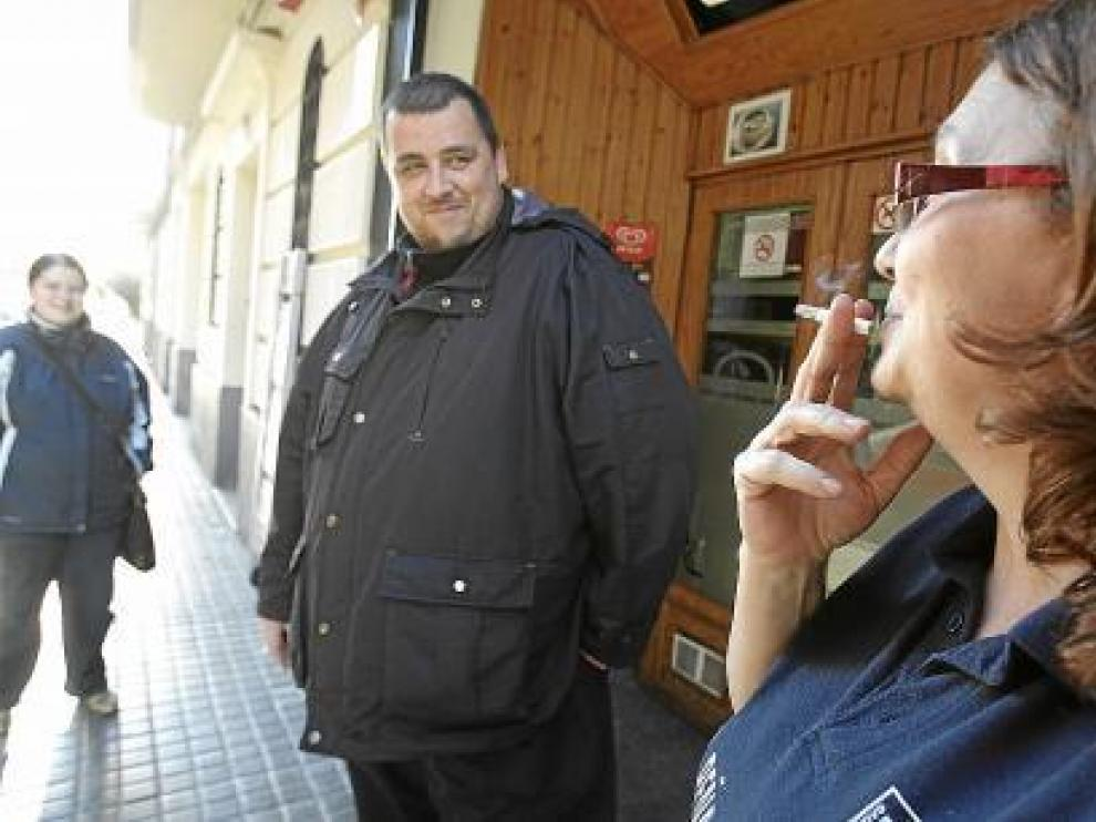 Una fumadora a la puerta de un bar.