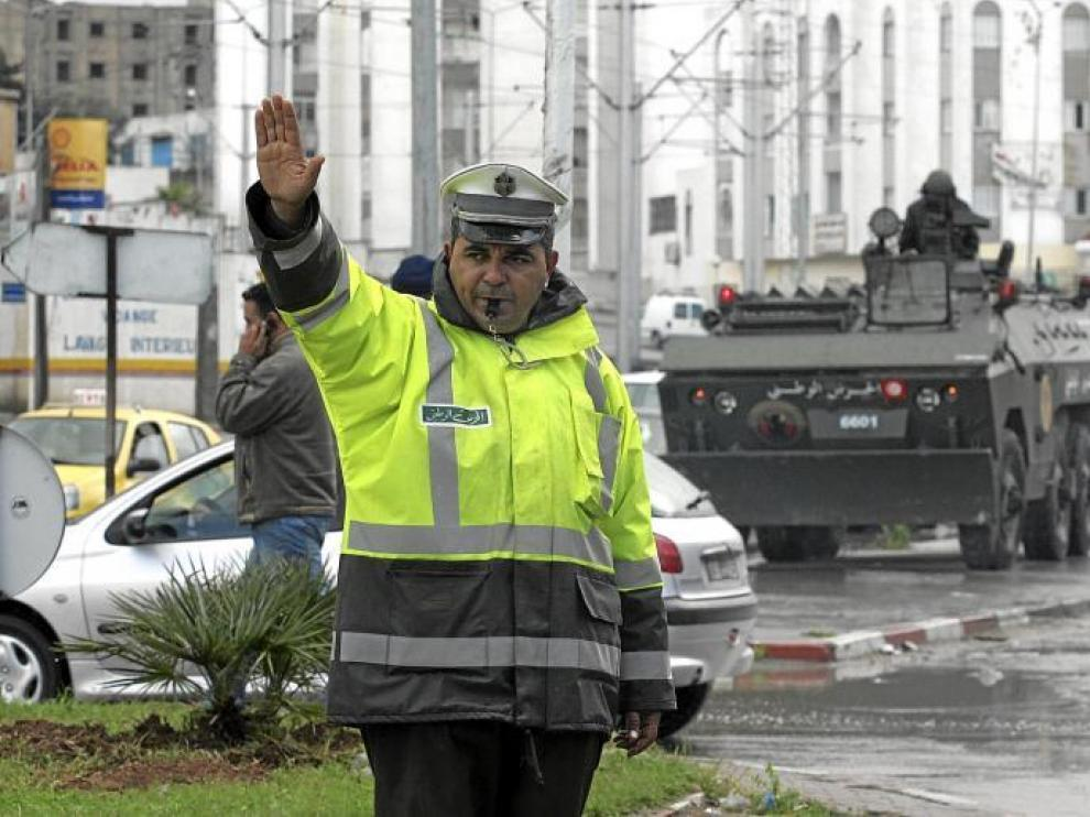 Un agente regula el tráfico en la capital tunecina ante una de las tanquetas que tomaron ayer las calles de la ciudad.
