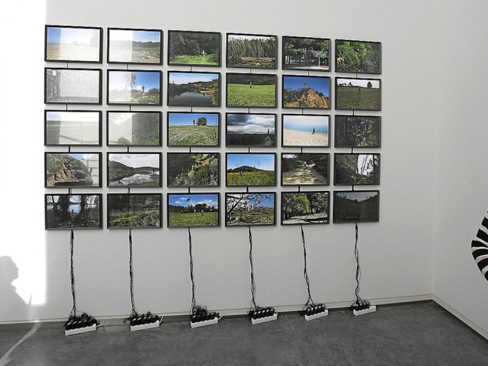 Alberto Gusi muy cerca de una espectacular instalación seriada de fotografías.