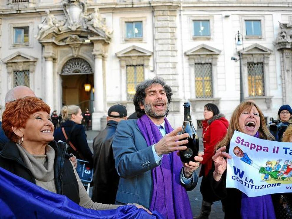 Miembros del movimiento Violeta anti-Berlusconi celebran en la calle la decisión del Tribunal Constitucional, ayer en Roma.