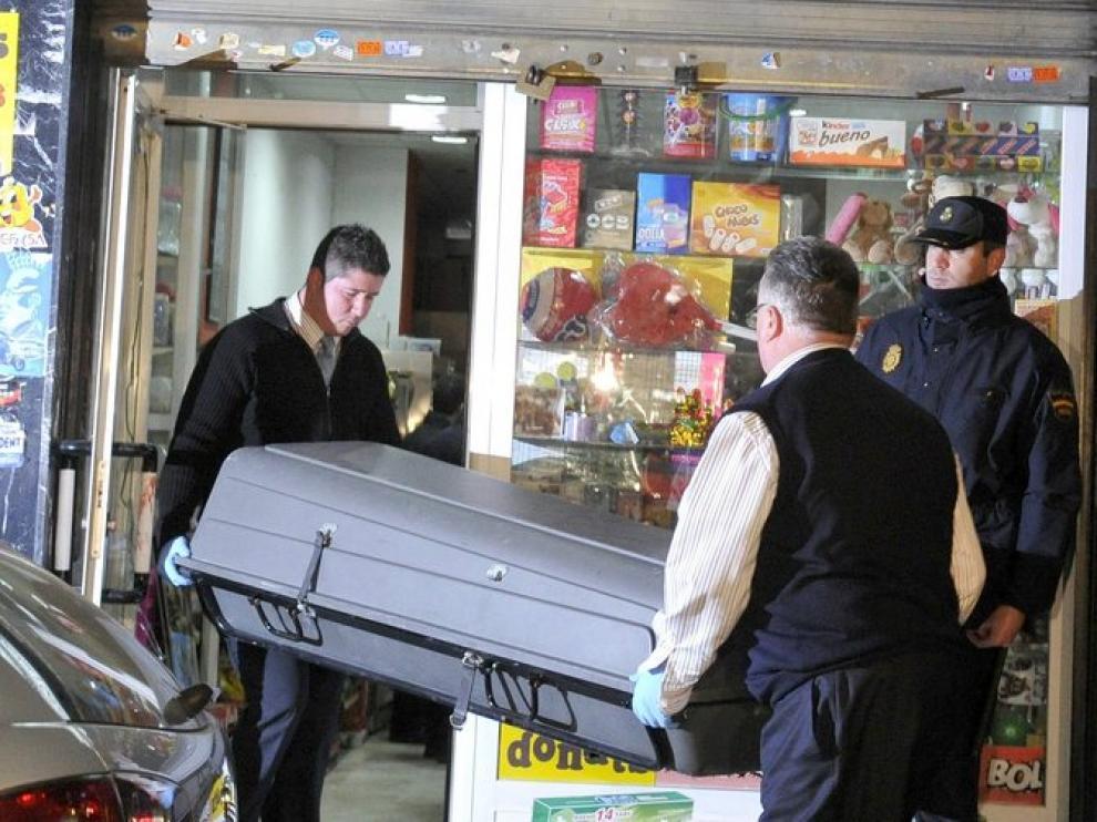 Miembros de la funeraria retiran el cuerpo de la mujer del establecimiento en el que trabajaba