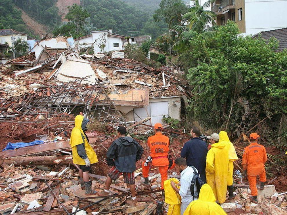Varias personas trabajan en las labores de limpieza tras los corrimientos de tierra por las lluvias