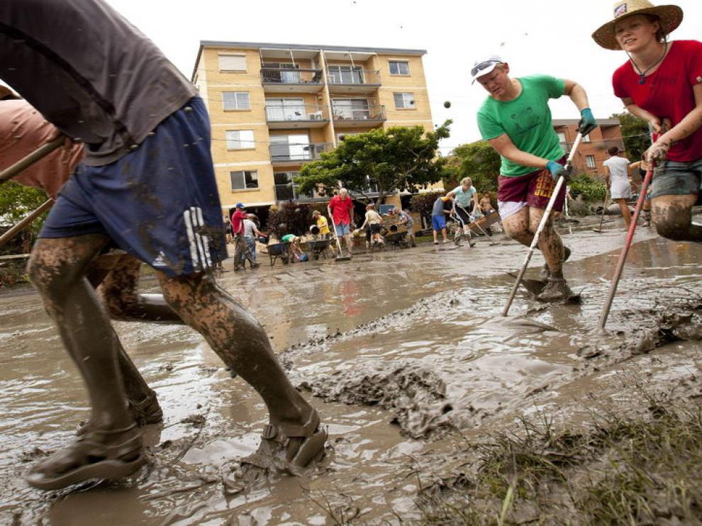 Varios ciudadanos retiran el lodo de las calles de la ciudad
