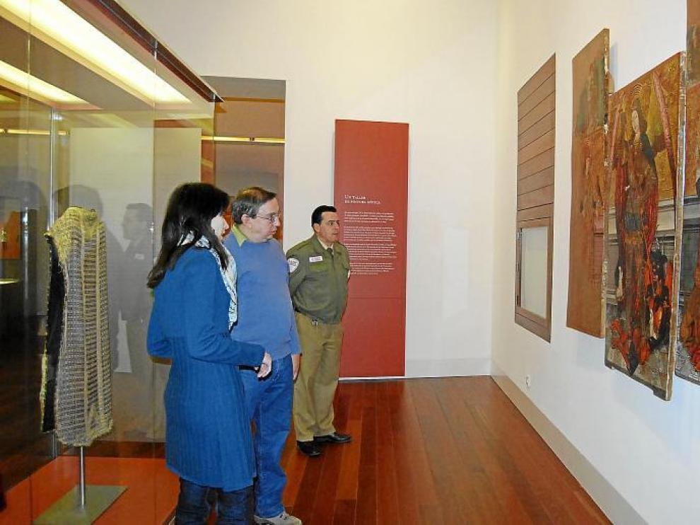 La guía del Museo Diocesano de Barbastro-Monzón explica las tablas pictóricas de estilo gótico a uno de los visitantes.
