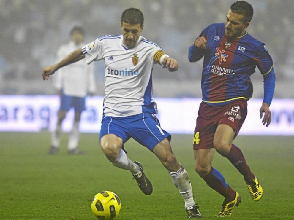 Gabi protege una pelota ante la acometida del centrocampista rival, Xavi Torres.