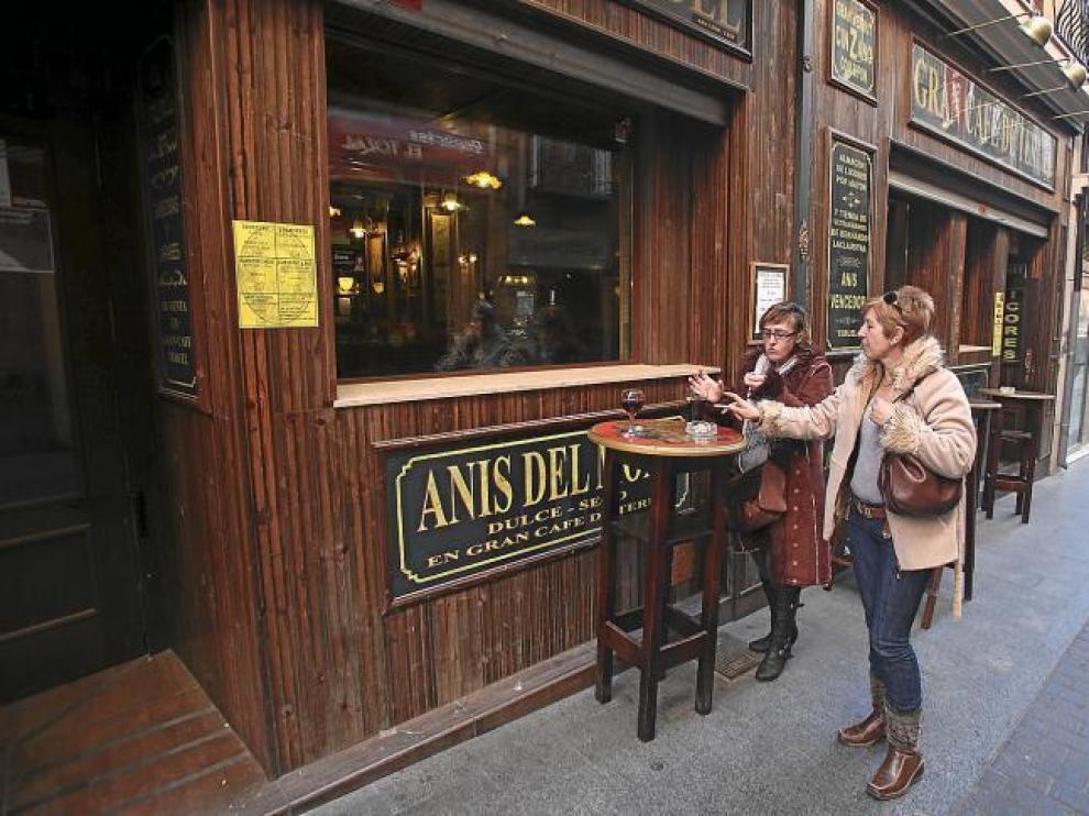 Dos clientes utilizan las mesas colocadas a las puertas de una céntrica cafetería para tomar una consumición sin dejar de fumar.