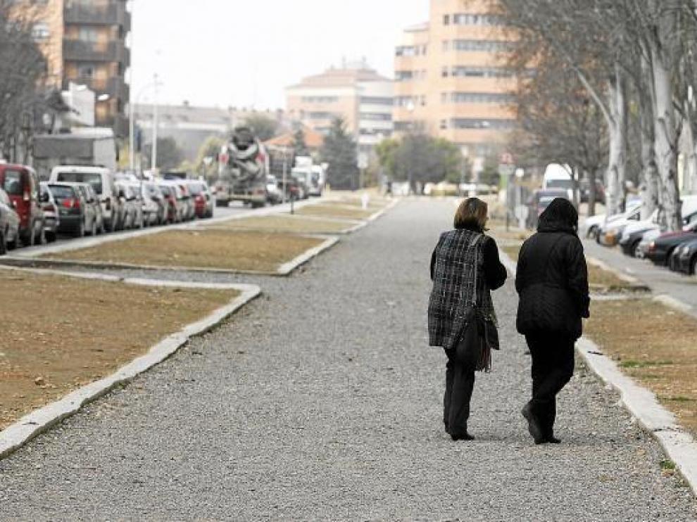 Dos mujeres caminan por el antiguo trazado de la vía ferroviaria en la calle Fuente del Ibón.
