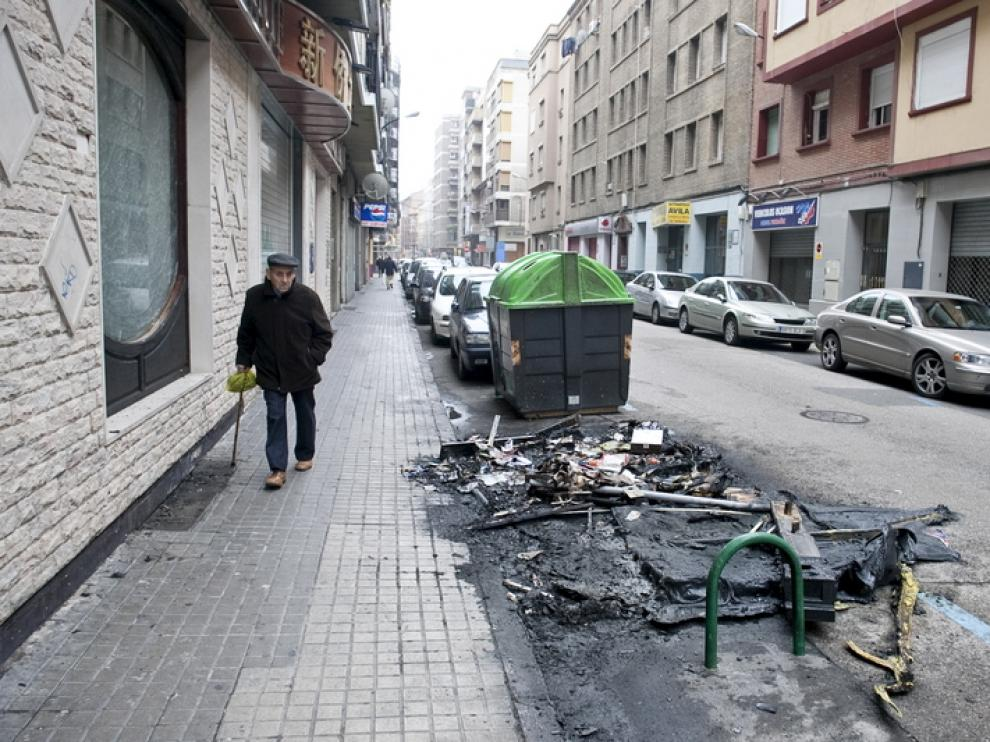 Restos de un contenedor quemado en la calle Ávila.