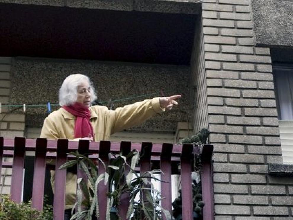Una mujer señala la fachada ennegrecida de su casa por el fuego