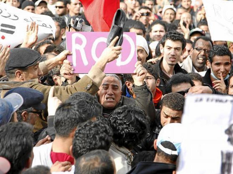 Tunecinos participan en una protesta contra el partido en el poder RCD, ayer en Túnez.
