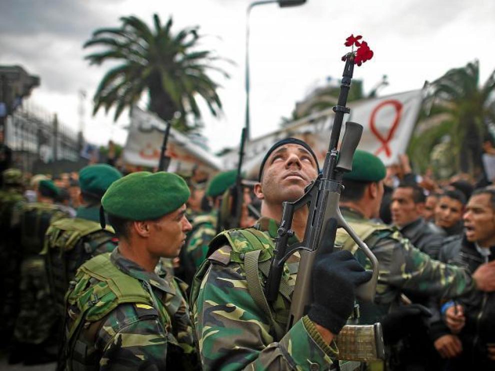 Un militar tunecino, con una flor en su arma, mira hacia el cielo durante la concentración ante la sede del partido RCD.