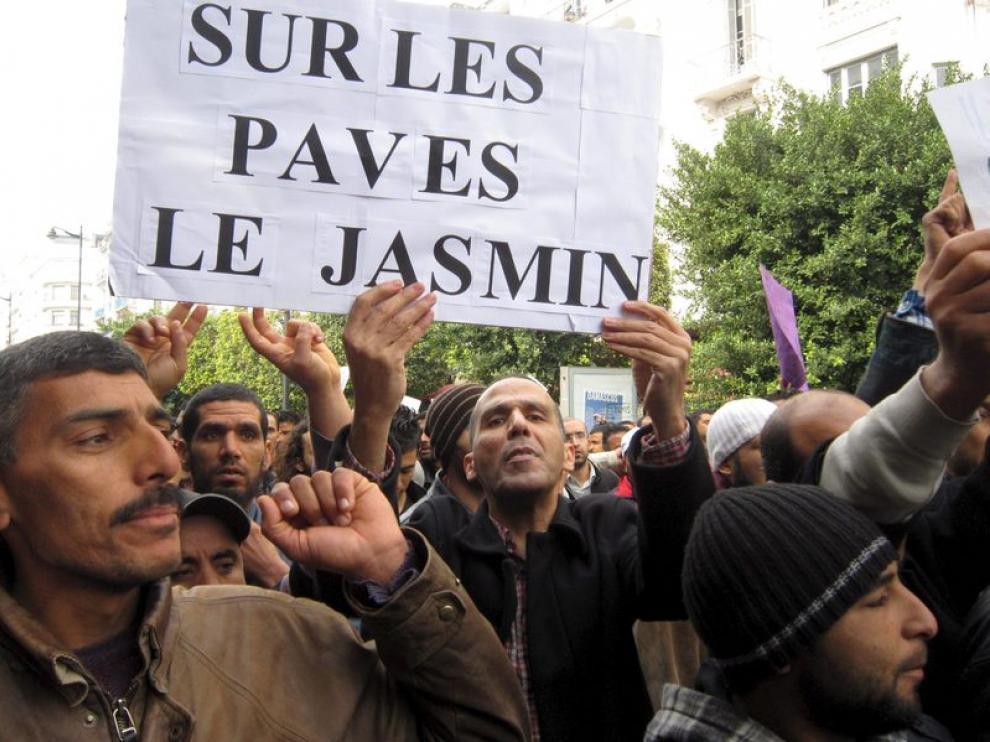 """Tunecinos se manifiestan con una pancarta que dice en francés """"Encima de las piedras, hay un jazmín"""""""