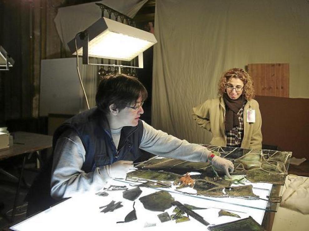 La restauradora Pilar Cano (izquierda) y la historiadora Susana Villacampa con parte de los cristales de la vidriera.